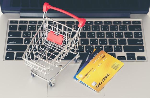 Carrinho de compras e cartão de crédito com o laptop na mesa