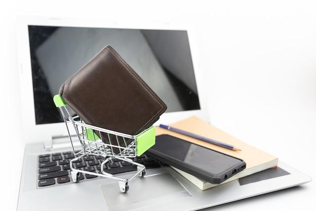 Carrinho de compras e carteira em fundo de notebook e laptop. compras online, poupança de investimento, compra, conceito de negócio.
