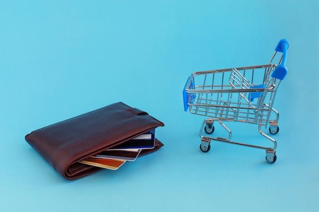 Carrinho de compras e cartões de crédito na carteira no fundo azul.