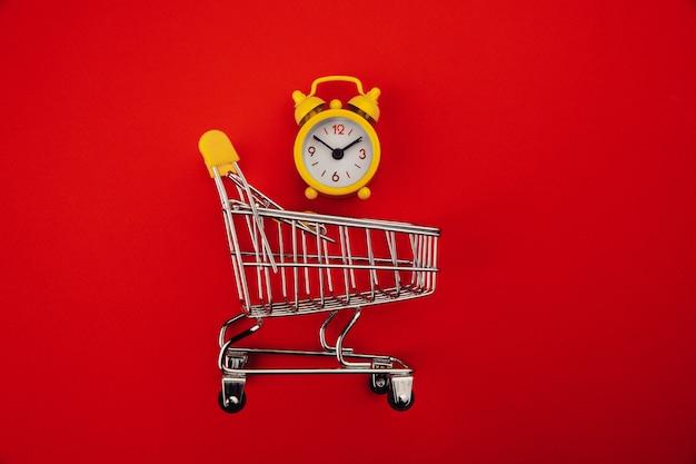 Carrinho de compras e despertador isolado no vermelho.