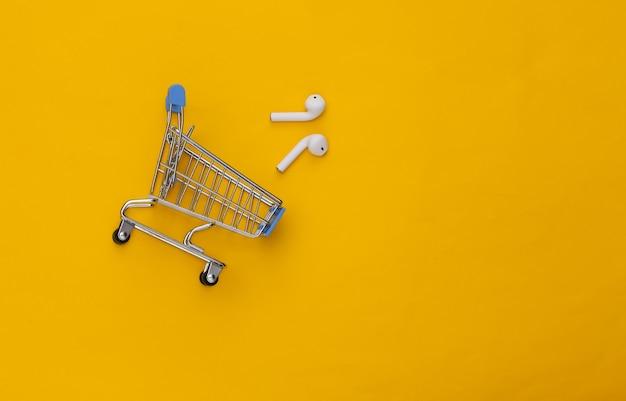 Carrinho de compras e fones de ouvido sem fio modernos em fundo amarelo.