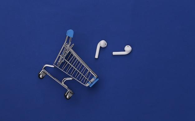 Carrinho de compras e fones de ouvido sem fio modernos no fundo azul clássico.