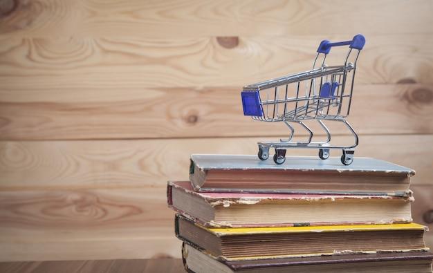 Carrinho de compras e livros na mesa de madeira.