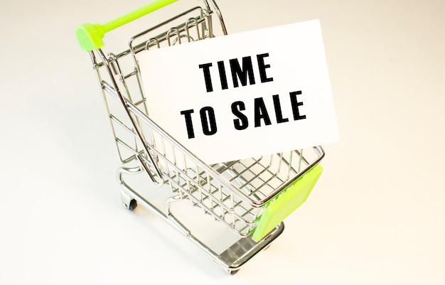 Carrinho de compras e o texto hora de venda em papel branco sobre fundo branco