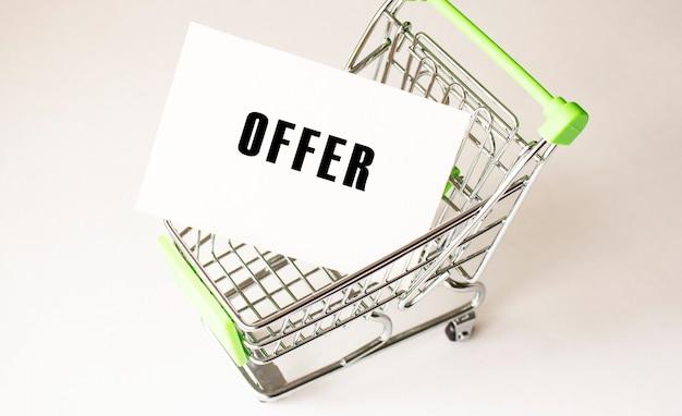 Carrinho de compras e oferta de texto em papel branco