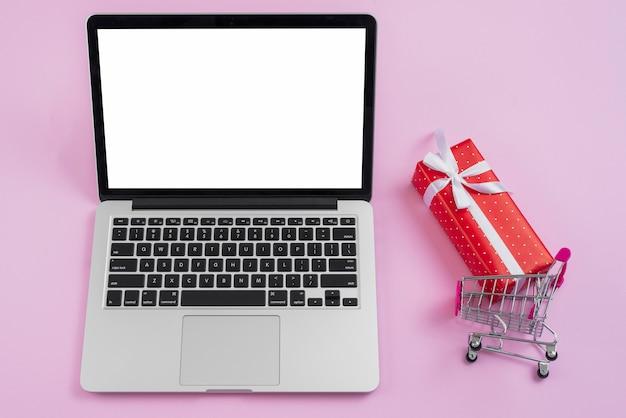 Carrinho de compras e pequeno presente perto de laptop