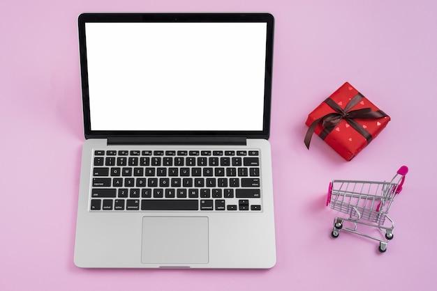 Carrinho de compras e presente perto de laptop