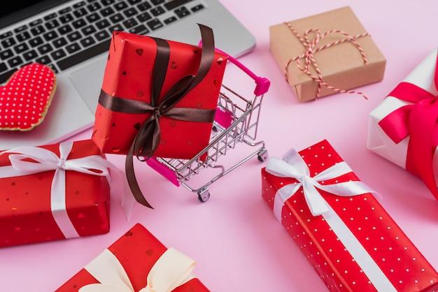 Carrinho de compras e presentes perto de laptop