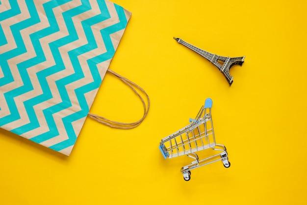 Carrinho de compras e saco de papel em fundo amarelo. conceito de cliente feliz. compra pela internet. loja online. consumismo, estilo de vida