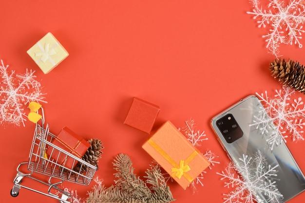 Carrinho de compras e smartphone com três câmeras, decoração de natal em um fundo vermelho, caixas de presentes, flocos de neve e telefone, descontos de natal e ano novo e conceito de presentes