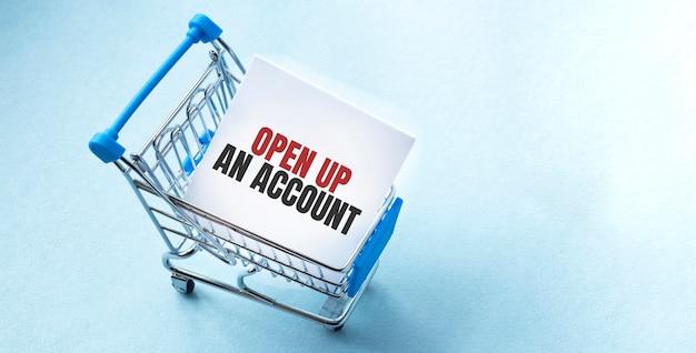 Carrinho de compras e texto abrir uma conta na lista de notas do papel branco