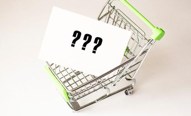 Carrinho de compras e texto em papel branco. conceito de lista de compras sobre fundo claro.