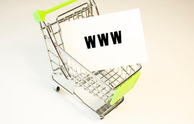 Carrinho de compras e texto www em papel branco