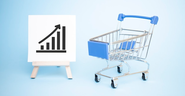 Carrinho de compras e um cavalete com um gráfico de tendências positivo em preto.