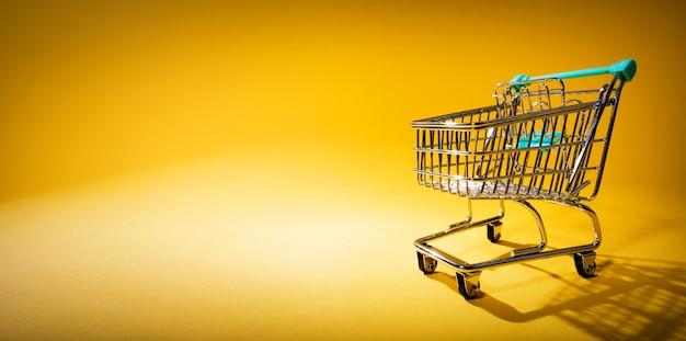 Carrinho de compras em fundo amarelo em destaque