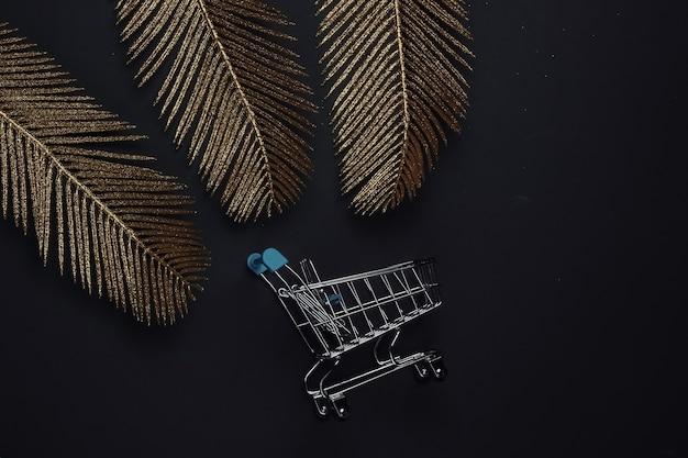 Carrinho de compras em fundo preto com folhas de palmeira douradas. moda plana lay. sexta-feira preta. vista do topo