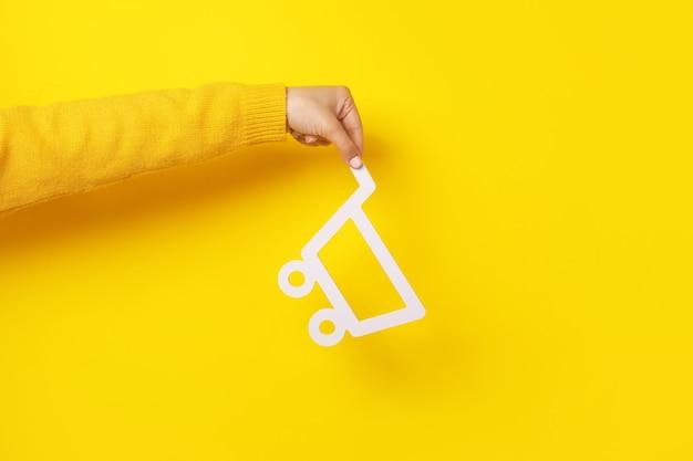 Carrinho de compras em mãos sobre fundo amarelo