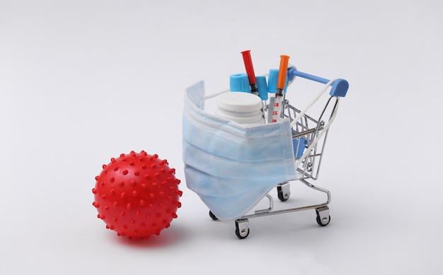 Carrinho de compras em máscara médica com tubos de ensaio, seringas, frasco de comprimidos e modelo de cepa de vírus em fundo branco. cuidados de saúde