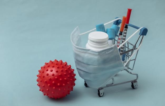 Carrinho de compras em máscara médica com tubos de ensaio, seringas, frasco de comprimidos e modelo de cepa de vírus em um fundo azul. cuidados de saúde