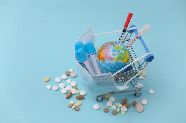 Carrinho de compras em máscara médica com tubos de ensaio, seringas, pílulas e um globo sobre um fundo azul. saúde global
