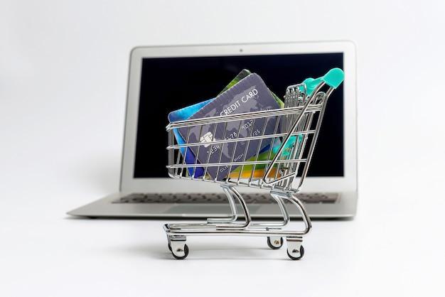 Carrinho de compras em miniatura com cartões de crédito ao lado do laptop, isolado em uma superfície clara