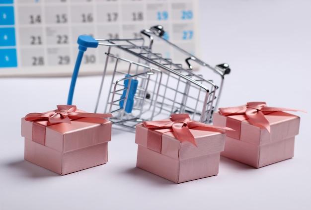 Carrinho de compras em miniatura e caixas de presente com calendário de mesa em fundo branco. compras de fim de ano, sexta-feira negra, conceito de oferta especial mensal