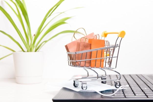 Carrinho de compras em miniatura em um laptop preto com pequenas sacolas de papel