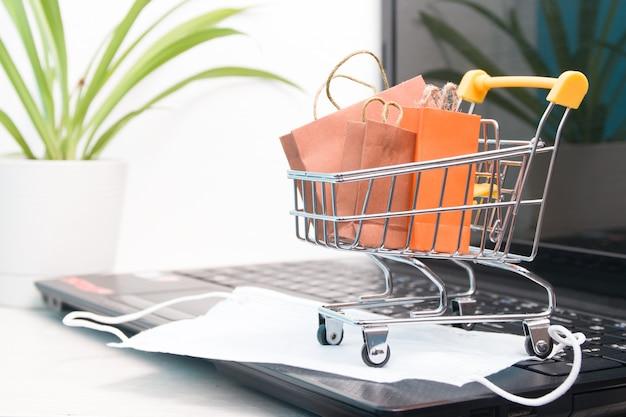 Carrinho de compras em miniatura em um laptop preto com sacolas de compras