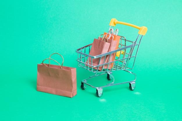 Carrinho de compras em miniatura em uma superfície verde