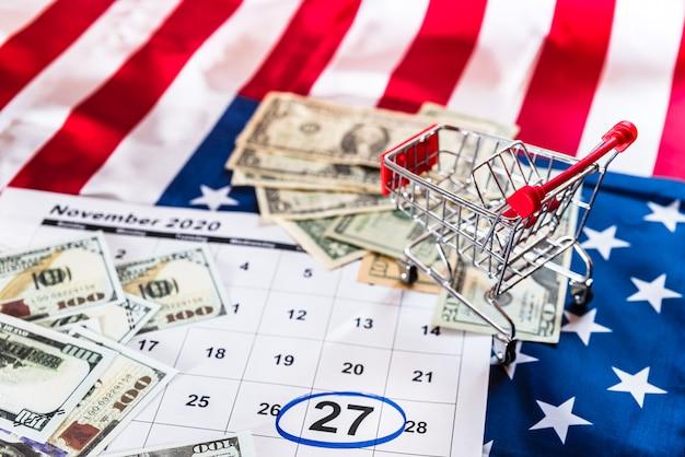 Carrinho de compras em um calendário marcado com notas de dólar
