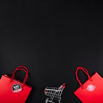 Carrinho de compras entre sacos vermelhos