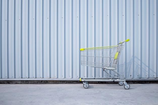 Carrinho de compras estacionado na parede de chapa de metal em frente a um supermercado