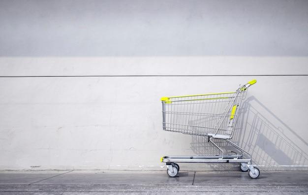 Carrinho de compras estacionado na parede de tijolos cinza em frente a um supermercado