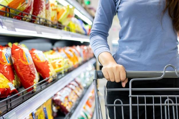 Carrinho de compras feminino empurrando no supermercado
