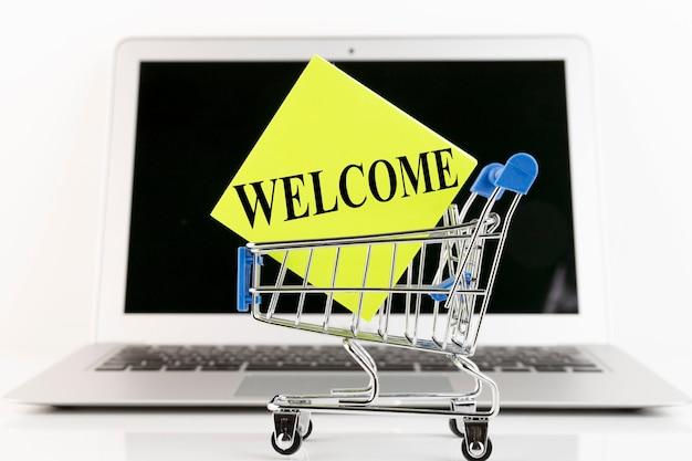 Carrinho de compras, laptop, texto, bem-vindo, em papel amarelo. conceito de negócios. copie o espaço