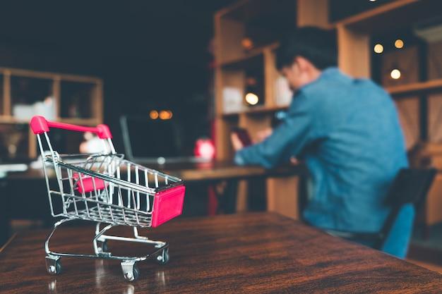 Carrinho de compras na tabela de madeira na loja, na compra em linha e no conceito do comércio eletrónico.