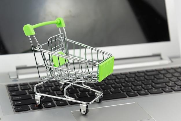 Carrinho de compras no fundo do laptop. compras, investimento, conceito de compra.