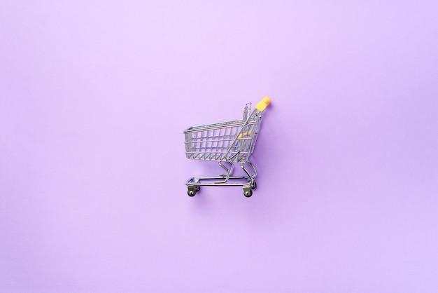 Carrinho de compras no fundo roxo. estilo minimalista. carrinho de loja no supermercado.