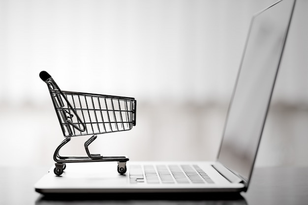 Carrinho de compras no laptop, compras on-line e conceito de serviço de entrega.