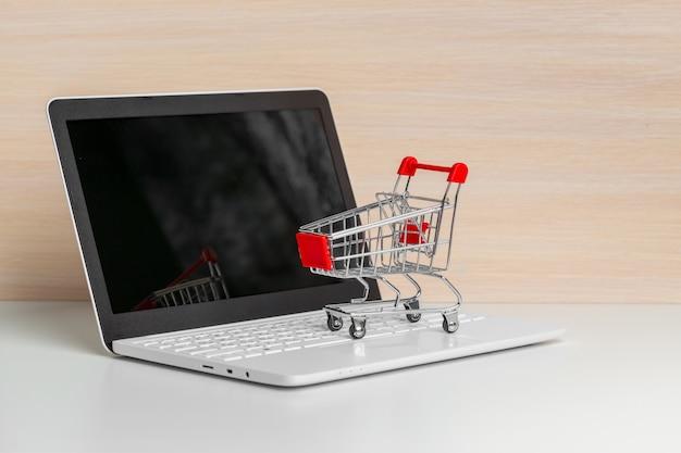 Carrinho de compras no laptop na mesa de madeira