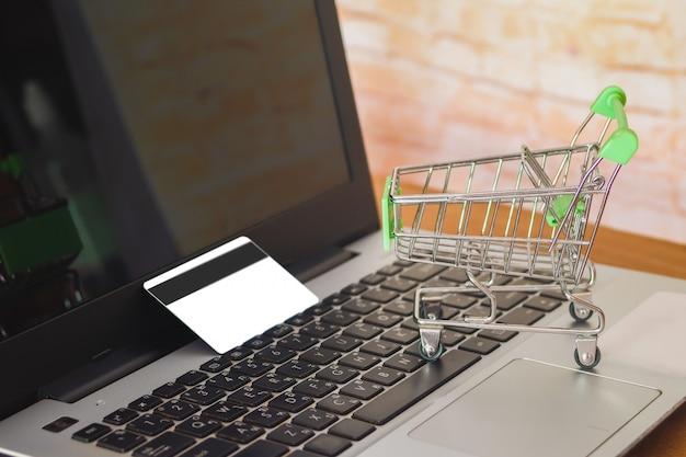 Carrinho de compras no teclado do portátil com cartão de crédito, conceito em linha da compra.