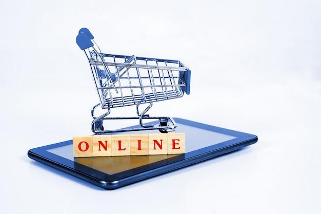 Carrinho de compras ou carrinho de metal no tablet móvel para compras on-line e comércio eletrônico.
