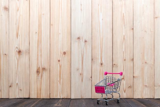 Carrinho de compras ou carrinho de supermercado na mesa de madeira