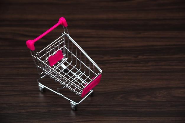 Carrinho de compras ou trole do supermercado na sala escura, conceito da compra da finança do negócio.