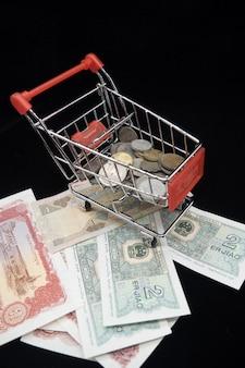 Carrinho de compras pequeno com a moeda em cédulas com fundo preto.