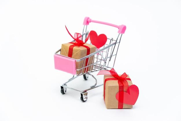 Carrinho de compras pequeno com caixas de presente em fundo branco. dê presentes com amor no dia dos namorados