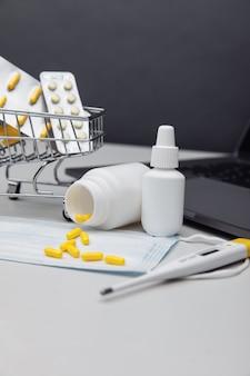 Carrinho de compras pequeno com comprimidos. compra online do conceito de medicamentos. imagem vertical.
