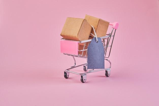 Carrinho de compras pequeno com etiqueta de preço em branco sobre um fundo rosa. carrinho de compras cheio de pacotes.