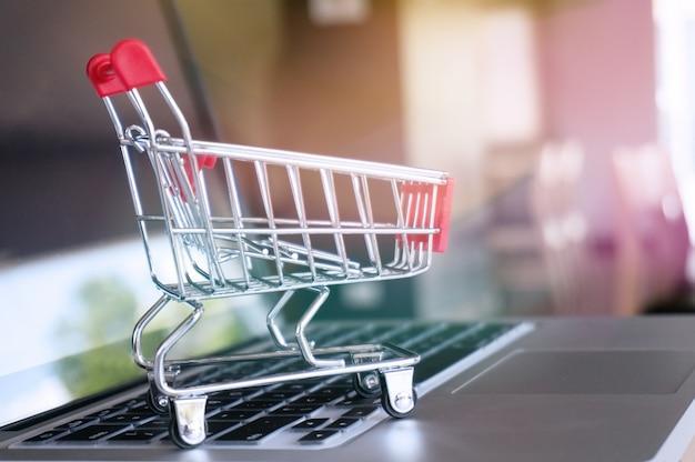 Carrinho de compras pequeno com laptop para compras on-line conceito.