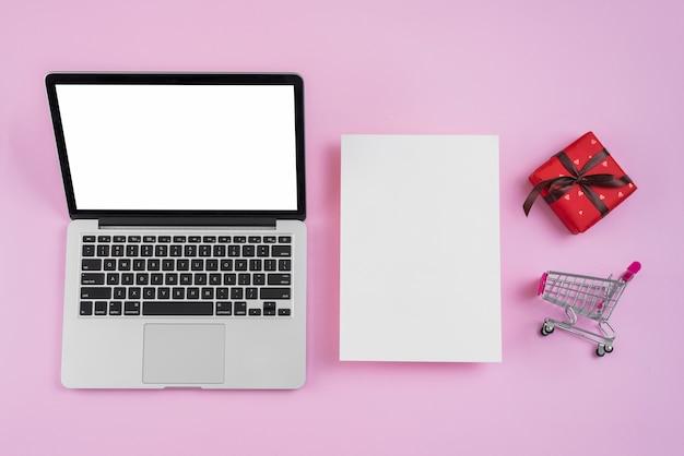 Carrinho de compras pequeno e presente perto de papel e laptop